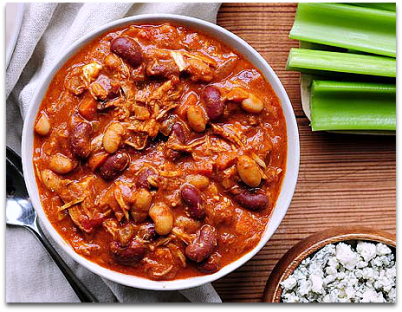 Flat lay bowl of buffalo chicken chili with celery stalks and crumbled feta cheese