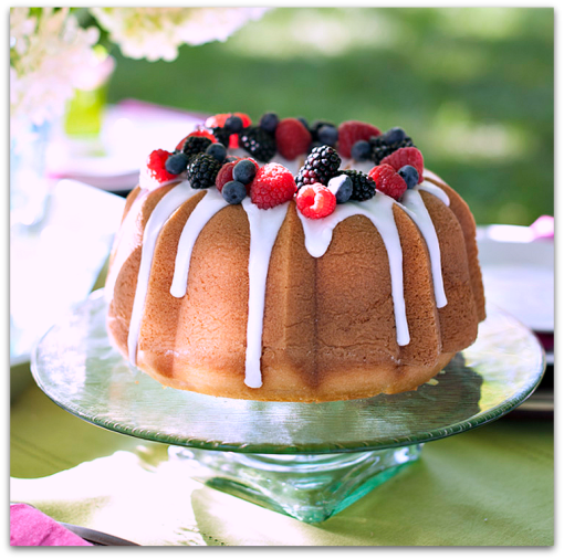 Bundt cake with white glaze, red and black raspberries on top.