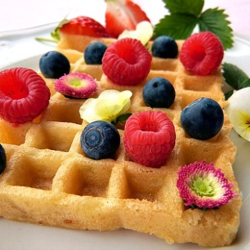 Waffle with fresh red raspberries, blueberries & edible flowers